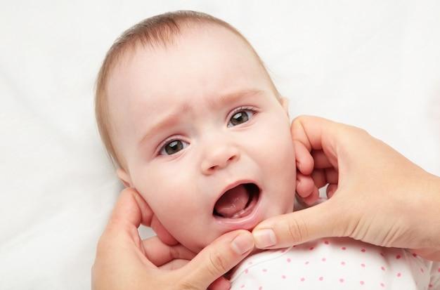 Die ersten beiden zähne des babys, die die eltern tragen müssen, um den mund sauber zu halten. Premium Fotos