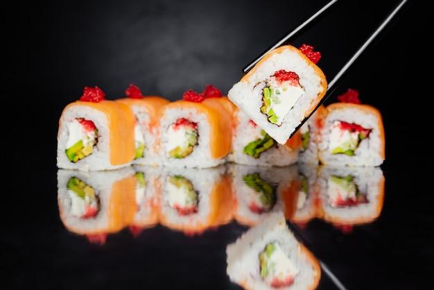 Die essstäbchen, die sushi halten, rollen philadelphia auf dem schwarzen hintergrund, der vom lachs gemacht wird Kostenlose Fotos