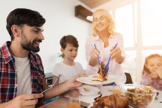 Die familie sitzt am festlichen tisch zum erntedankfest. Premium Fotos