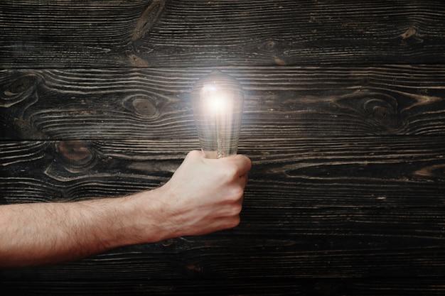 Die faust der männer mit leuchtender glühlampe auf dunklem hölzernem hintergrund. das konzept mutiger ideen Premium Fotos