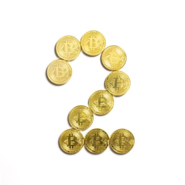 Die figur von 2 aus bitcoin-münzen ausgelegt und auf weißem hintergrund isoliert Kostenlose Fotos