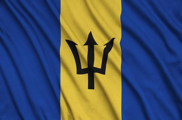 Die flagge von barbados ist auf einem sportstoff mit vielen falten abgebildet. Premium Fotos