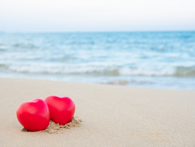 Die form mit zwei herzen, die auf den sand am strand und am blauen meer gesetzt wurde, verwischte hintergrund Premium Fotos