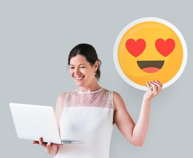 Die frau, die ein herz hält, mustert emoticon und einen laptop Kostenlose Fotos