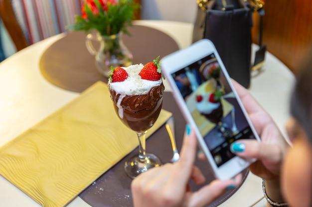Die frau, die fotos des köstlichen eiscremeweißes macht, mischt erdbeere mit einem intelligenten telefon. Premium Fotos