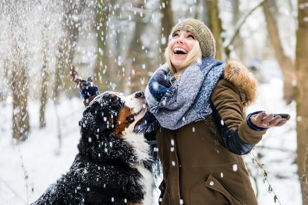 Die frau, die ihren hund im winter geht, und beide erforschen den schnee zu Premium Fotos
