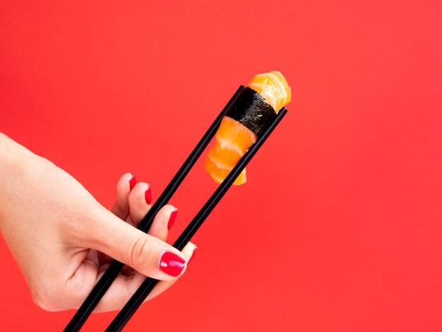 Die frau, die im hieb hält, haftet ein lachssushi auf einem roten hintergrund Kostenlose Fotos