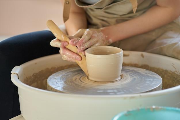 Die frau, die keramische tonwaren auf rad, handnahaufnahme macht, konzentrieren sich auf töpfer, palmen mit tonwaren Premium Fotos