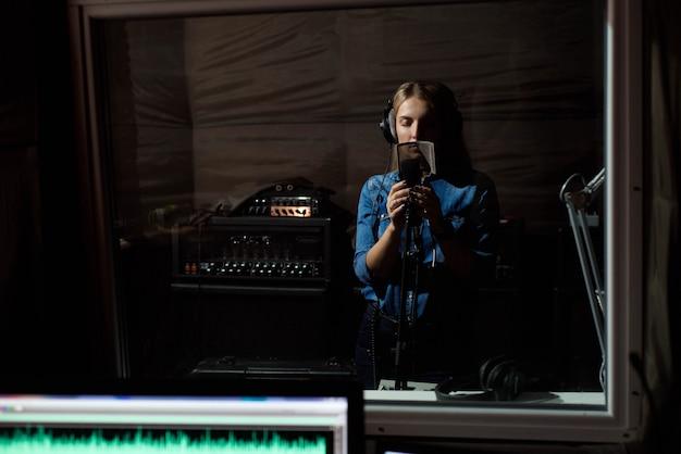 Die frau, die singt, singen mit handy am tonstudio. du Premium Fotos