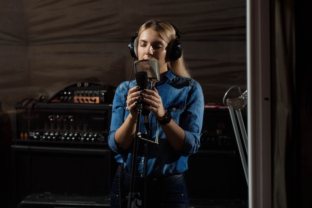 Die frau, die singt, singen mit handy am tonstudio. Premium Fotos