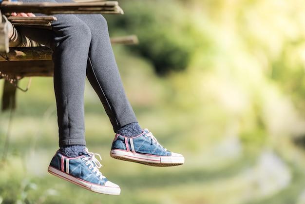 Die frau, die sitzt und entspannt sich auf holzfußboden mit den beinen, die unten hängen. Premium Fotos