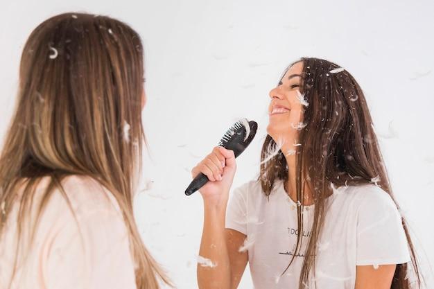 Die frau, die zu ihrem freund schaut, singen das lied, das kamm wie ein mikrofon hält Kostenlose Fotos