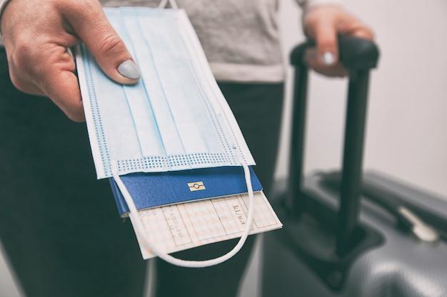 Die frau hält den reisepass mit der fahrkarte und der medizinischen maske als wesentliche voraussetzung für reisen in der zeit nach 19 jahren Premium Fotos