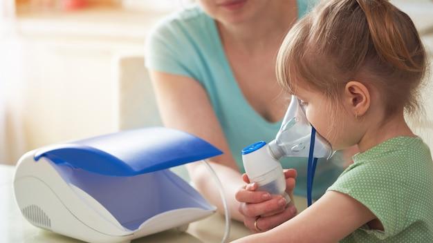Die frau hilft dem kind durch die maske zu atmen Premium Fotos