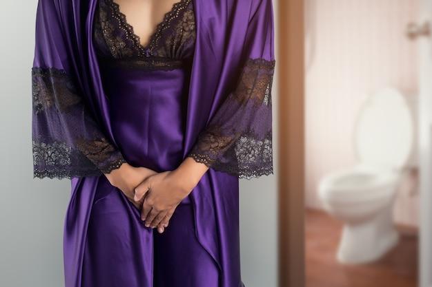 Die frau in lila satin nachtwäsche und bademantel aufwachen für zur toilette gehen Premium Fotos