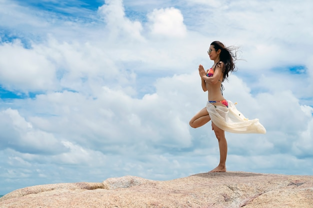 Die frau mit yoga-haltung am strand Premium Fotos