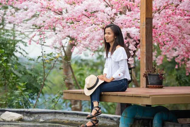 Die frau sitzt unter dem kirschbaum Kostenlose Fotos