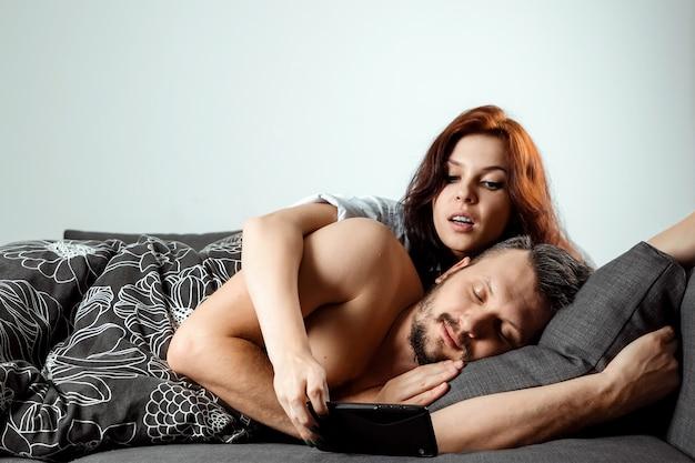 Die frau spioniert das telefon ihres mannes aus, während er schläft Premium Fotos