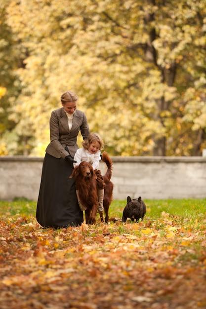 Die frau und das kind in der vintage-kleidung gehen im park mit hunden Premium Fotos