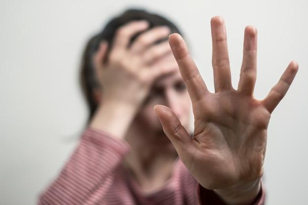 Die frau zeigt nein von hand, lehnt belästigungen ab. das mädchen bedeckt ihr gesicht. Premium Fotos