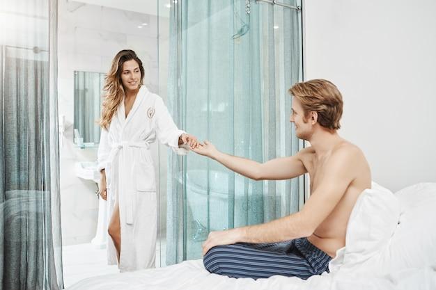 Die freundin kommt aus dem badezimmer und trägt einen bademantel, hält die hand, die ihr freund streckt, und lächelt ihn an. paar flirtet und teilt ihre liebe im hotelzimmer. Kostenlose Fotos