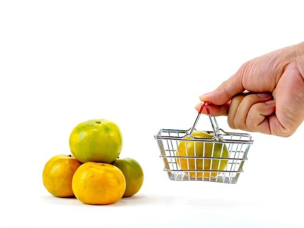 Die frischen orangen und der warenkorb, korbeinkaufskonzept mit weißem hintergrund Premium Fotos