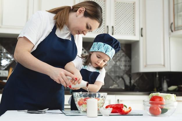 Die fürsorgliche mutter bringt ihrer kleinen tochter bei, wie man in der küche einen salat zubereitet Premium Fotos