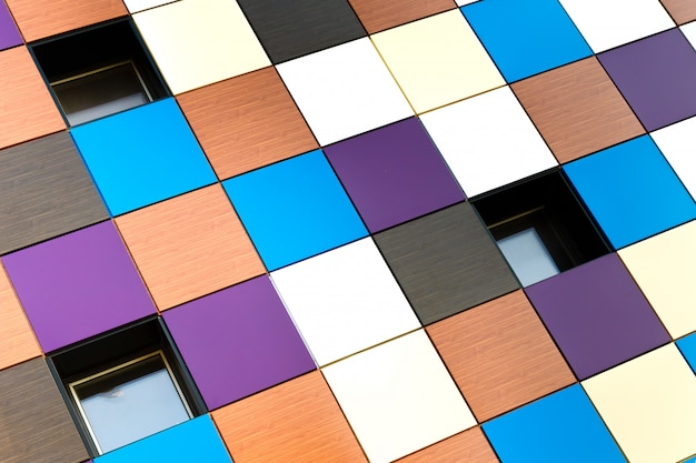 Die gebäudewand besteht aus mehrfarbigen quadratischen paneelen Premium Fotos