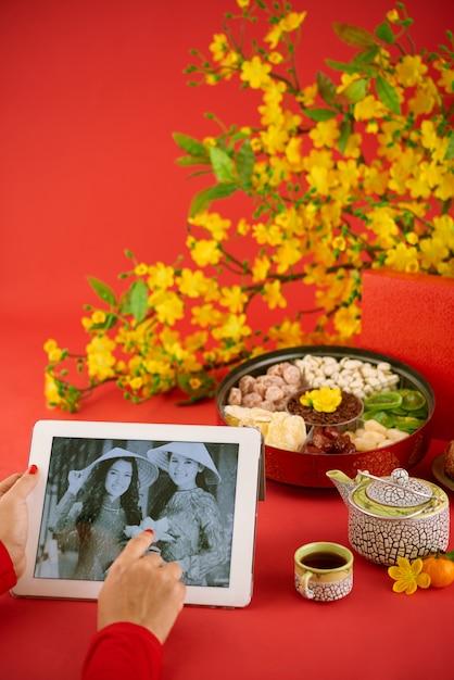 Die geerntete unerkennbare frau, die bei tisch sitzt, diente dem traditionellen betrachten alter fotos auf dem digitalen vorsprung gegen den roten hintergrund Kostenlose Fotos
