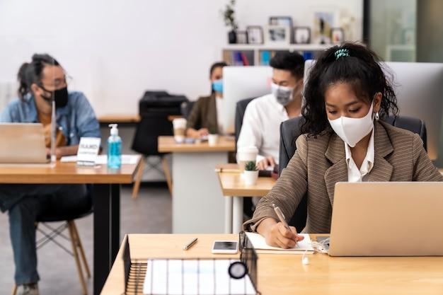 Die gemischte rasse der afrikanischen schwarzen und asiatischen geschäftsfrau trägt eine gesichtsmaske, die in einem neuen normalen büro mit sozialer distanz zu einer gruppe von geschäftsteammitgliedern arbeitet, um die ausbreitung des coronavirus covid-19 zu verhindern Premium Fotos