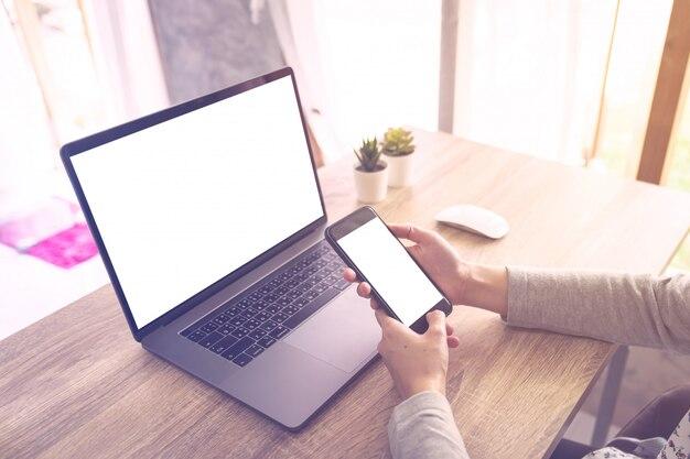 Die geschäftsfrau, die laptop-computer verwendet, tun on-line-tätigkeit und halten telefon auf hölzerner tabelle. Premium Fotos