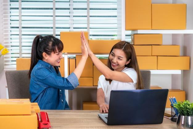 Die geschäftsfrau mit zwei asiaten des jugendlichinhabers arbeitet zu hause für das on-line-einkaufen und betrachtet und aufgeregt in der bestellung am laptop und mit büroausstattung, unternehmerlebensstilkonzept Premium Fotos