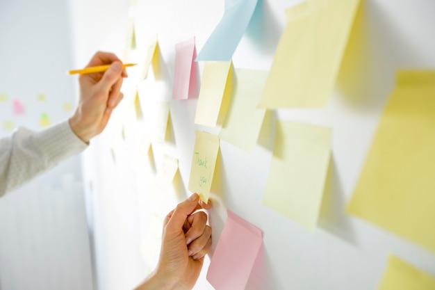 Die geschäftsleute, die am büroposten sich treffen, färbten anmerkungsaufkleber auf dem brett. brainstorming-konzept. Premium Fotos