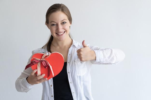 Die glückliche dame, die sich herz zeigt, formte geschenkbox und daumen Kostenlose Fotos