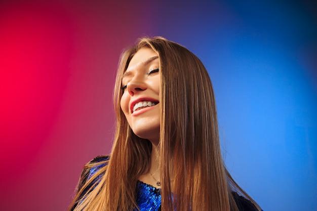 Die glückliche frau, die gegen farbige wand steht und lächelt Kostenlose Fotos