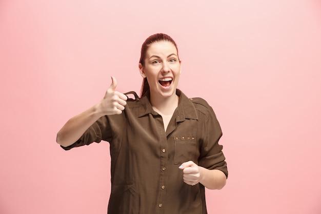 Die glückliche geschäftsfrau, die gegen rosa wand steht und lächelt. Kostenlose Fotos