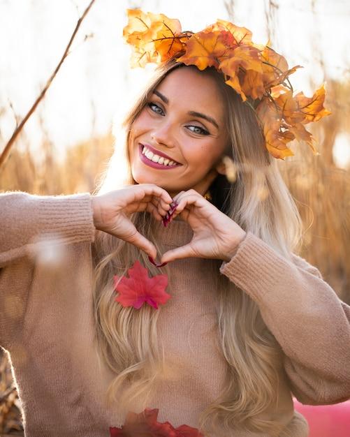 Die glückliche junge frau, die herz lächelt und macht, formen mit der hand an draußen Kostenlose Fotos