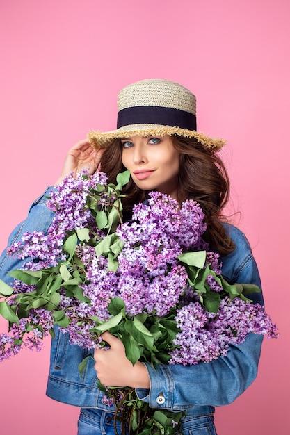 Die glückliche lächelnde frau, die geruch der blumenstraußflieder genießt, blüht vorbei Premium Fotos