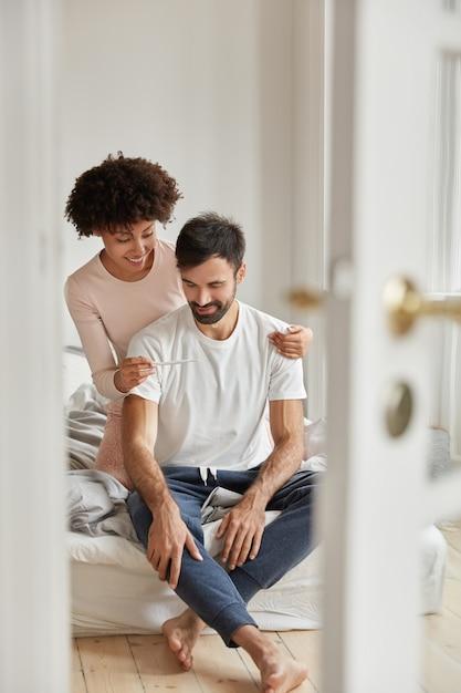 Die glückliche schwarze frau zeigt dem ehemann einen schwangerschaftstest, ist mit dem positiven ergebnis zufrieden, posiert im schlafzimmer einer modernen wohnung, freut sich über gute nachrichten und ist bereit, eltern zu werden. familienpaar drinnen. elternschaft Kostenlose Fotos