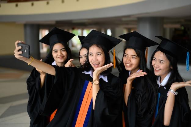 Die graduierende studentengruppe trug bei der abschlussfeier der universität einen schwarzen hut. Premium Fotos