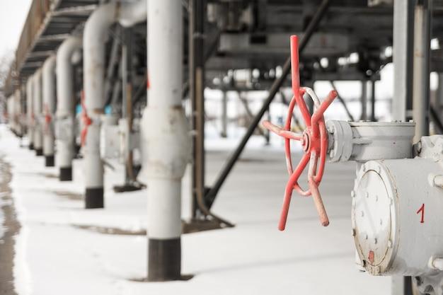 Die grauen metallrohre für die gaszufuhr mit roten ventilen an der gaskompressorstation schossen im winter. der blick auf eine rohrkonstruktion für den gastransport an der gaskompressorstation im winter Premium Fotos