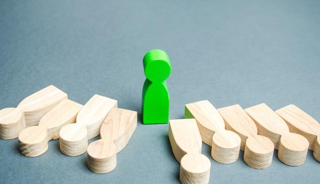 Die grüne figur eines mannes steht zwischen den lügnern. erfolgreiche wahl. Premium Fotos