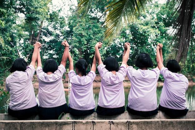 Die gruppe der einheitlichen studenten, die glücklich hände zusammenhalten. konzept der besten freunde Premium Fotos
