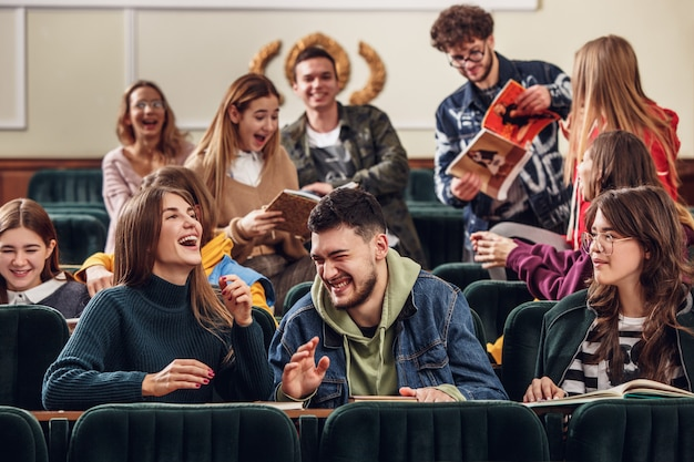 Die gruppe fröhlicher, fröhlicher schüler, die vor dem unterricht in einem hörsaal sitzen Kostenlose Fotos