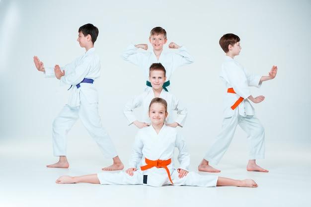 Die gruppe von jungen und mädchen, die beim aikido-training in der kampfkunstschule kämpfen. gesunder lebensstil und sportkonzept Kostenlose Fotos