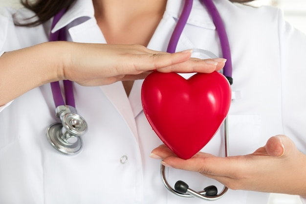 Die hände der ärztinnen halten rotes herz vor ihrer brust. nahaufnahme der hand des doktors. medizinische hilfe, prophylaxe oder versicherungskonzept. Premium Fotos