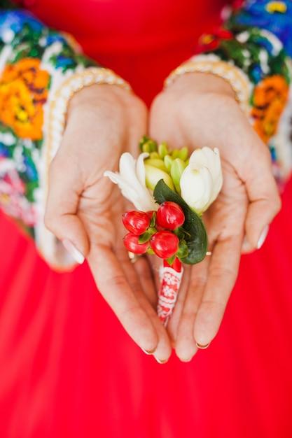 Die hände der braut halten den boutonniere ihres bräutigams Kostenlose Fotos