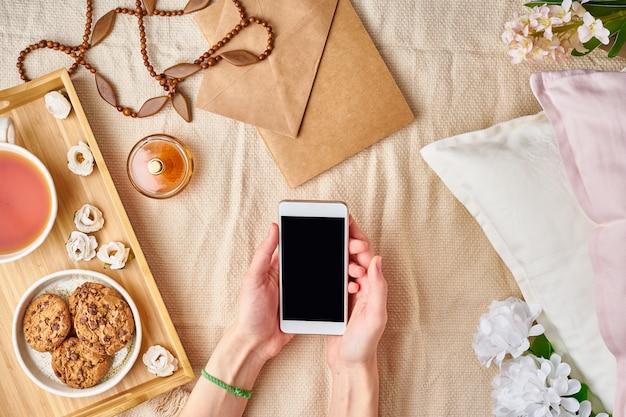 Die hände der flatlay-frauen, die einen smartphone halten. gemütliches zuhause, urlaub, wochenende Premium Fotos