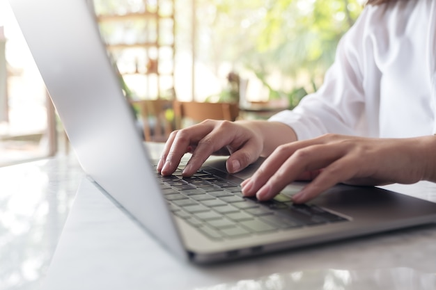 Die hände der frau, die auf laptoptastatur auf tabelle mit unschärfenaturhintergrund arbeiten und schreiben Premium Fotos