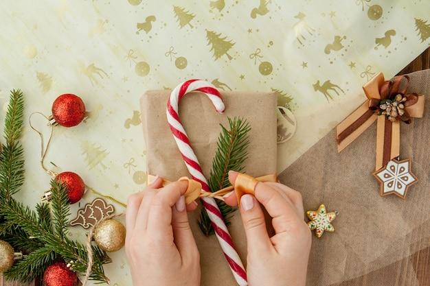 Die hände der frau, die oben weihnachtsgeschenk, abschluss einwickeln. unvorbereitete weihnachtsgeschenke auf hölzernem mit dekorelementen und einzelteilen, draufsicht. weihnachten oder neujahr diy verpackung. Premium Fotos
